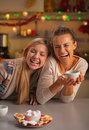 Smiling two girlfriends having christmas snacks in christmas dec decorated kitchen Stock Images