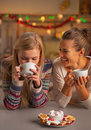 Smiling two girlfriends having christmas snacks in kitchen decorated Stock Images