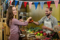 Smiling vendor giving tomatoes to woman at the counter in the grocery store Royalty Free Stock Photo