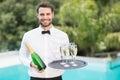 Smiling waiter holding champagne flutes and bottle Royalty Free Stock Photo