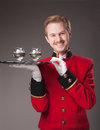 Smiling waiter in red uniform with a tray with glasses on a grey background Stock Photography