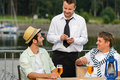 Smiling waiter taking order men customers outdoor bar Royalty Free Stock Image