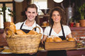 Smiling waiter and waitress holding basket full of bread rolls Royalty Free Stock Photo