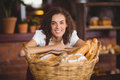 Smiling waitress bended over a basket of bread Royalty Free Stock Photo