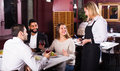 Smiling waitress and guests at the table Royalty Free Stock Photo