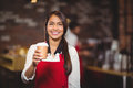 Smiling waitress handing a take-away mug Royalty Free Stock Photo