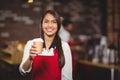 Smiling waitress handing a take-away mug Royalty Free Stock Photo