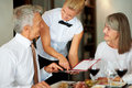 Smiling waitress helping senior couple Stock Images