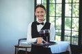 Smiling waitress holding a tray with glasses of red wine in restaurant Royalty Free Stock Image