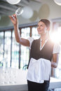 Smiling waitress holding up a empty wine glass Royalty Free Stock Photo