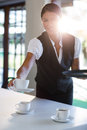 Smiling waitress serving cup of coffee Royalty Free Stock Photo