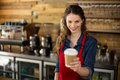 Smiling waitress serving a cup of coffee to customer in café Royalty Free Stock Photo