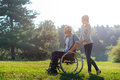 Smiling wife carrying wheelchair of her disabled husband