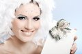 Smiling winter beauty with christmas present holding wearing fancy makeup and white feather hat Stock Photography