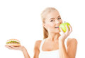 Smiling woman with apple and hamburger health beauty weightloss food diet concept sporty Stock Images