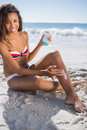 Smiling woman applying sun cream on her leg the beach Royalty Free Stock Images