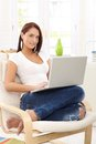 Smiling woman in armchair with computer pretty sitting laptop bright living room Stock Photo
