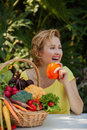 Smiling woman with basket full of vegetables outdoors. Healthy lifestyle.