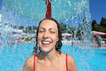 Smiling woman bathes in pool under water splashes Royalty Free Stock Photos