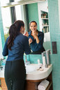 Smiling woman bathroom applying lipstick mirror businesswoman Royalty Free Stock Photo
