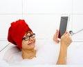 Smiling woman in bathtub with tablet computers close up Stock Photo