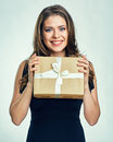 Smiling woman in black evening dress holding gift box.