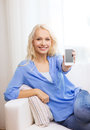 Smiling woman with blank smartphone screen at home technology advertising and internet concept sitting on couch Royalty Free Stock Photography