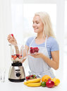 Smiling woman with blender preparing shake at home Royalty Free Stock Photo