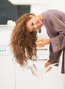Smiling woman blow drying hair in bathroom young modern Royalty Free Stock Photography
