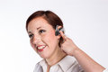 Smiling woman with bluetooth earpiece a young business red hair activates her Royalty Free Stock Image