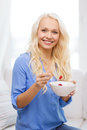 Smiling woman with bowl of muesli having breakfast healthcare food home and happiness concept at home Royalty Free Stock Photos