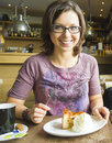 Smiling woman at cafe eating apple cake dessert with cream