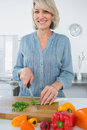 Smiling woman chopping vegetables at the kitchen counter Stock Photos