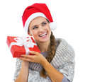 Smiling woman in christmas hat shaking christmas present box young sweater and Royalty Free Stock Photo
