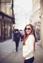 Smiling woman in the city pretty red haired young sunglasses Stock Photo
