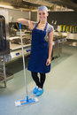 Smiling woman cleaning the kitchen floor