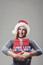 Smiling woman clutching a pile of xmas gifts pretty young in red santa hat colourful christmas for her loved ones in her arms Royalty Free Stock Images