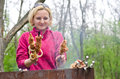 Smiling woman cooking kebabs over a BBQ fire