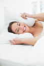 Smiling woman covering ears with pillow in bed portrait of a young Royalty Free Stock Image