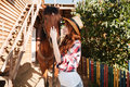 Smiling woman cowgirl taking care of her horse on farm Royalty Free Stock Photo
