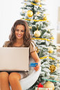 Smiling woman with credit card using laptop near christmas tree portrait of young Stock Image