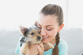 Smiling woman cuddling her yorkshire terrier puppy at home in the living room Stock Images