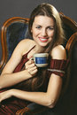 Smiling woman with a cup of coffee elegant dress is enjoying Stock Image