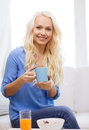 Smiling woman with cup of tea having breakfast healthcare food home and happiness concept glass juice and bowl muesli Stock Photo