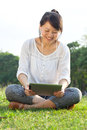 Smiling woman with digital tablet using and sitting in park Stock Photo