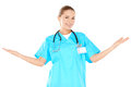 Smiling woman doctor raising her hands in green scrubs standing to the sides to indicate and include surroundings isolated on Royalty Free Stock Photography
