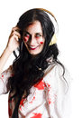 Smiling woman dress in blood splattered clothes listening to death metal music on headphones Royalty Free Stock Image