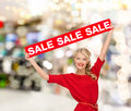 Smiling woman in dress with red sale sign shopping christmas and mall concept at shopping mall Royalty Free Stock Photo
