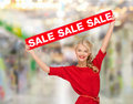 Smiling woman in dress with red sale sign shopping christmas and mall concept at shopping mall Stock Photo