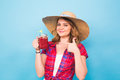 Smiling woman drink red juice. studio portrait with blue background and copy space Royalty Free Stock Photo